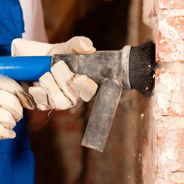 """""""Construction worker removing plaster"""" stock image"""