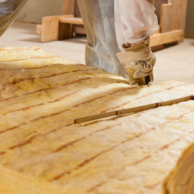 """""""Man cutting insulation material for building"""" stock image"""