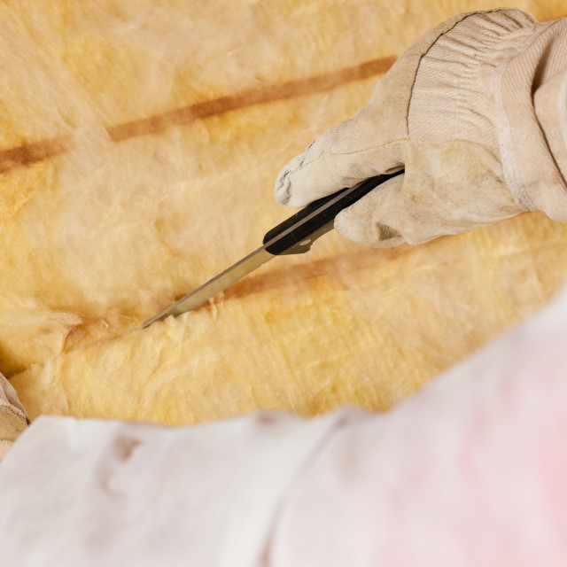 """Man cutting insulation material for building"" stock image"