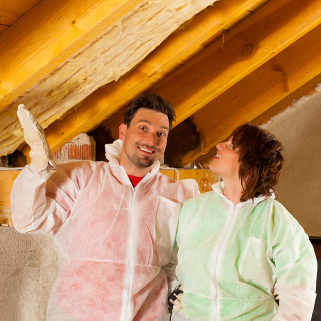 """Couple installing thermal insulation to roof"" stock image"