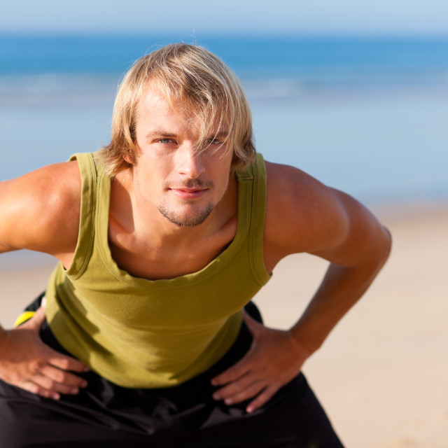 """Sportive man doing gymnastics on the beach"" stock image"