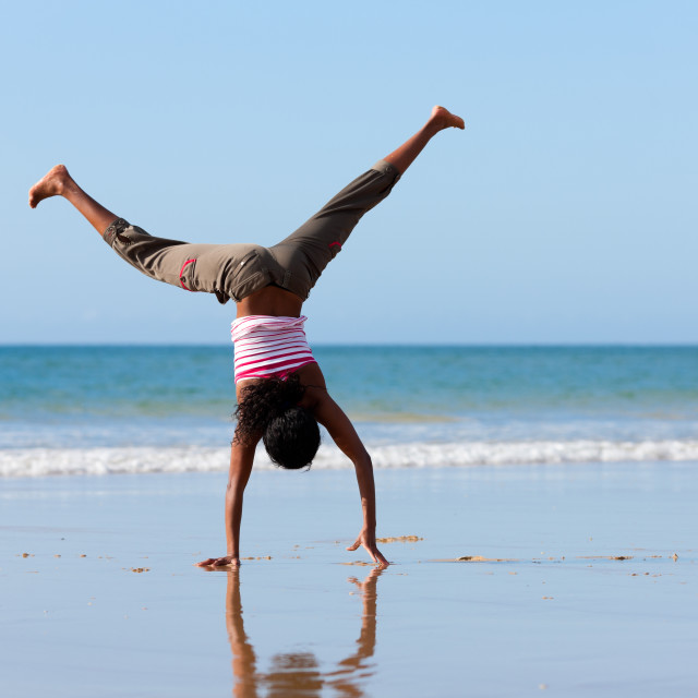"""Sportive woman doing gymnastics on the beach"" stock image"