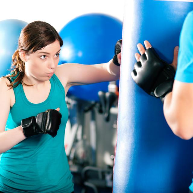 """Female kick boxer with trainer hitting sandbag"" stock image"