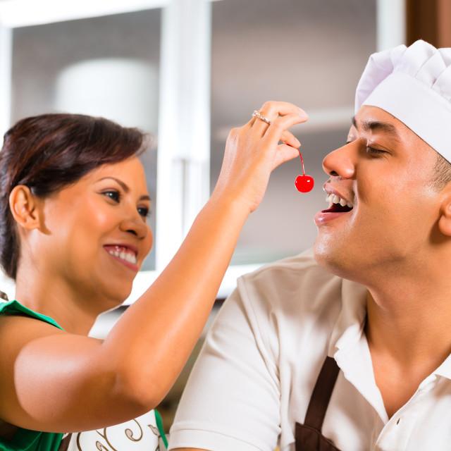 """Asian couple baking chocolate cake in kitchen"" stock image"