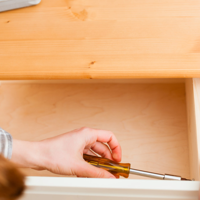 """Young woman is assembling a cupboard"" stock image"