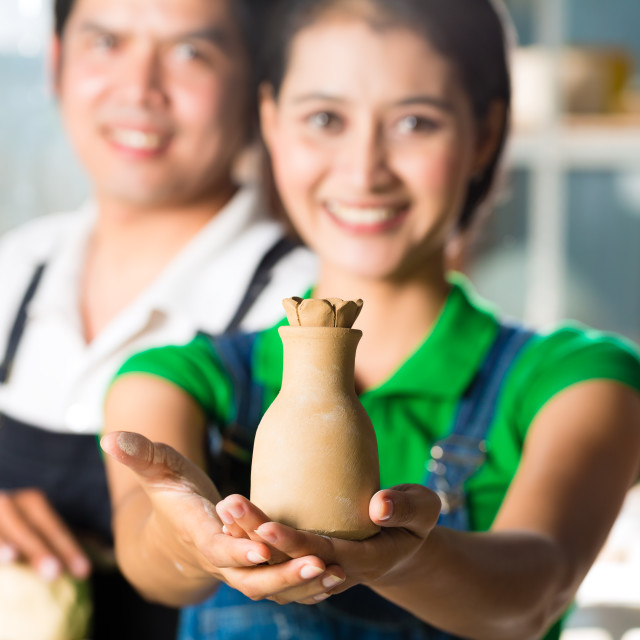 """Asians with handmade pottery in clay studio"" stock image"