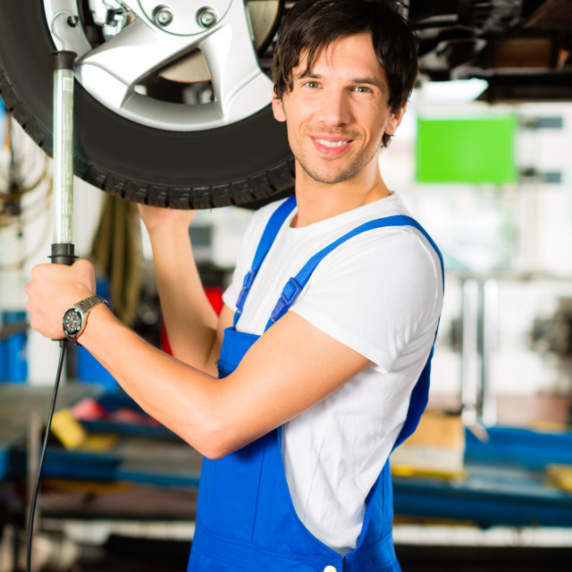 """""""Young mechanic in blue overall working on car"""" stock image"""