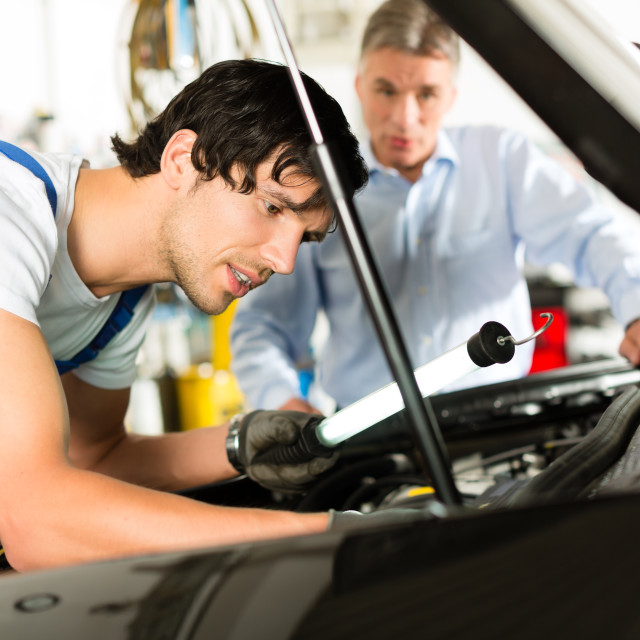 """Mature man and mechanic looking at car engine"" stock image"