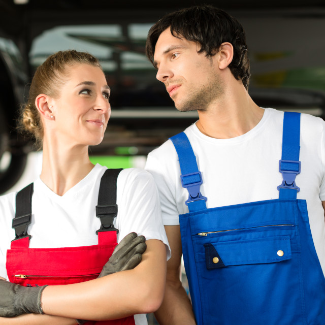 """Car mechanics male and female in front of auto"" stock image"