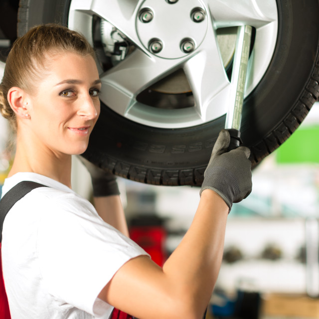 """Female car mechanic working on jacked auto"" stock image"