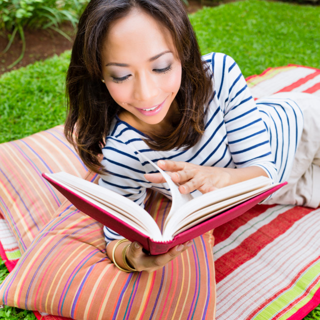 """Asian woman at home in garden reading book"" stock image"