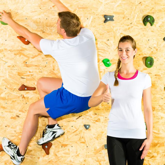 """""""Woman and man climbing at climbing wall"""" stock image"""
