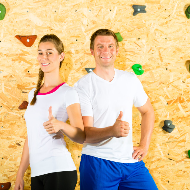"""Woman and man standing at climbing wall"" stock image"
