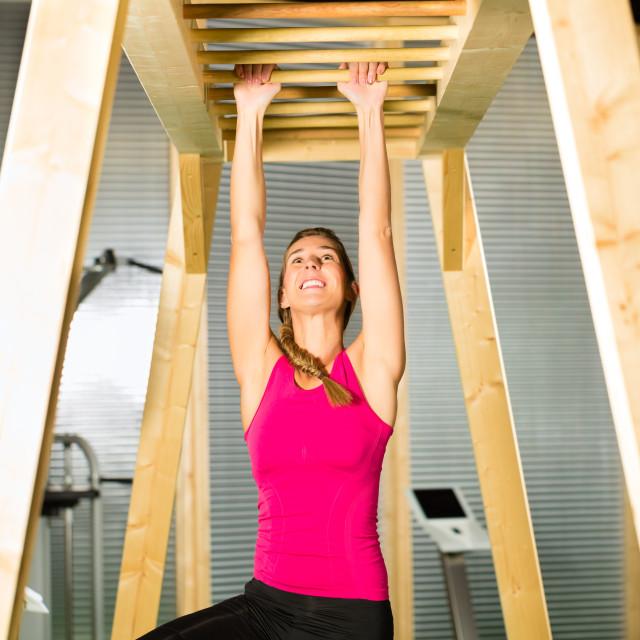 """Woman hanging at high or horizontal bar"" stock image"