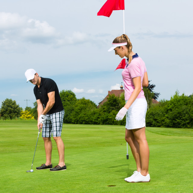 """Young sportive couple playing golf on a course"" stock image"