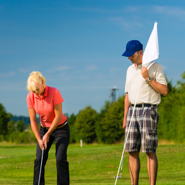 """""""Young sportive couple playing golf on a course"""" stock image"""