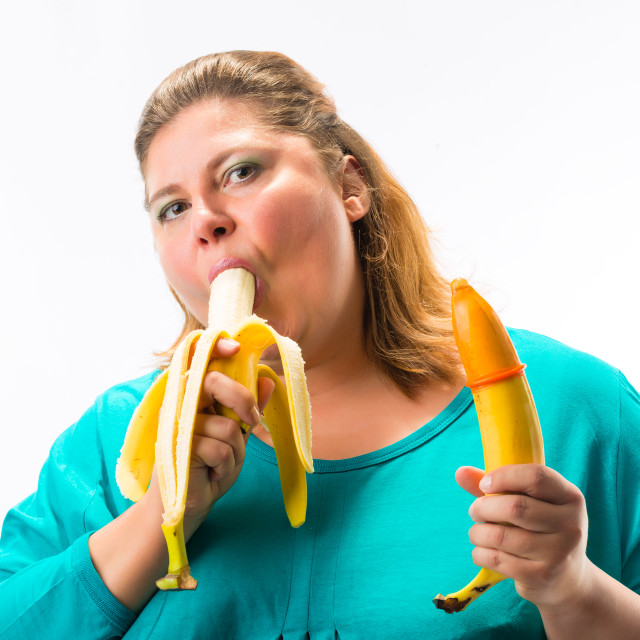 """""""Young woman holding banana with condom"""" stock image"""