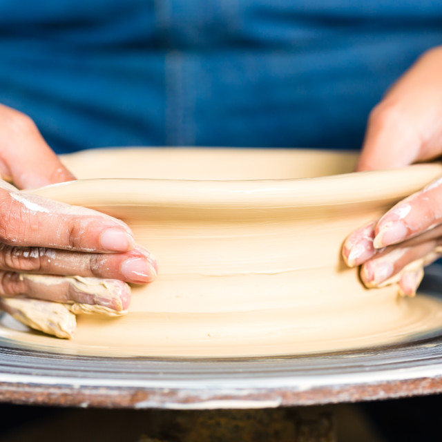 """Potter creating clay bowl on turning wheel"" stock image"