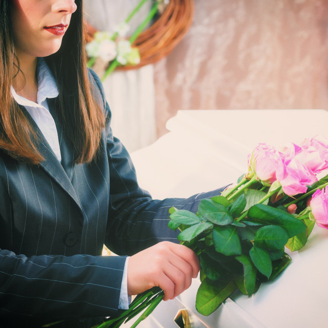 """Woman putting rose on coffin at funeral"" stock image"