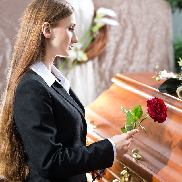 """Mourning Woman at Funeral with coffin"" stock image"
