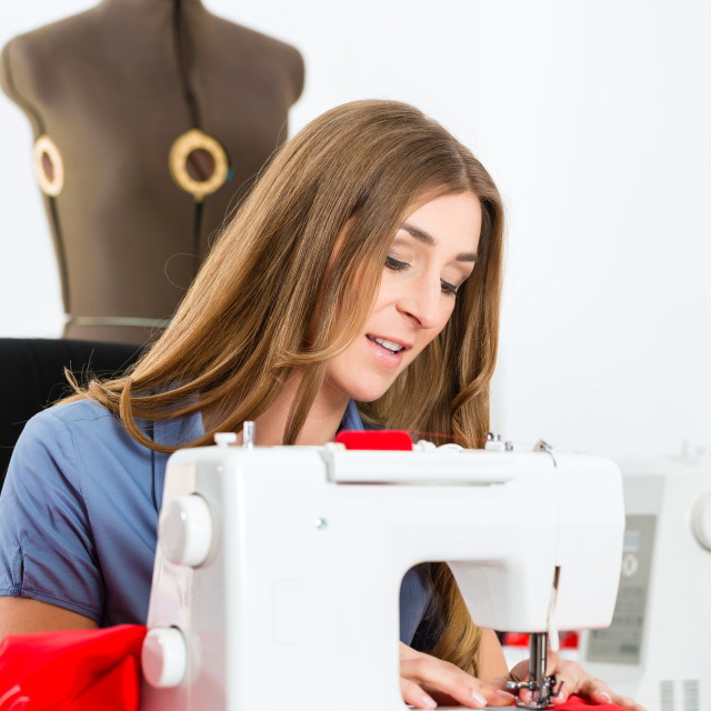 """Fashion designer or tailor working in studio"" stock image"
