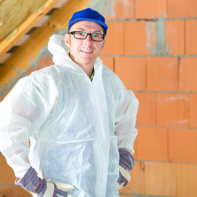 """Worker attaching thermal insulation to roof"" stock image"