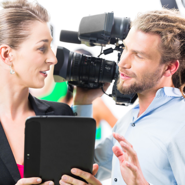 """Director giving cameraman direction for video production"" stock image"