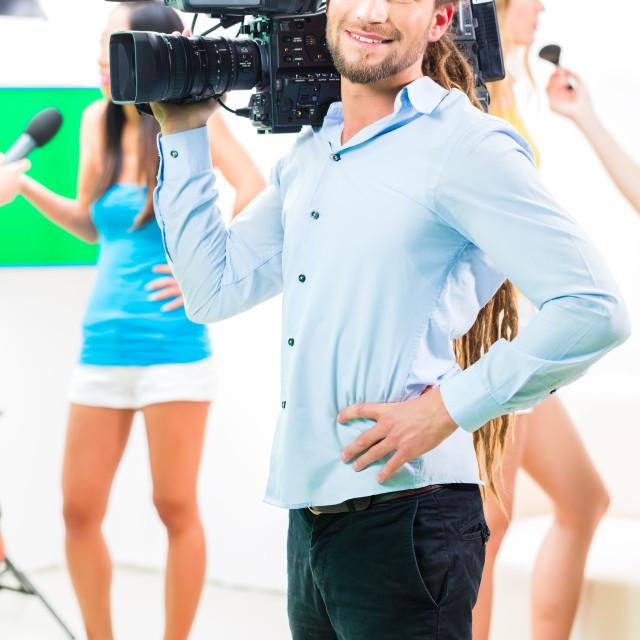 """Cameraman shooting with camera on film set"" stock image"