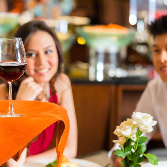 """Waiter serving Chinese couple red wine in fancy restaurant"" stock image"