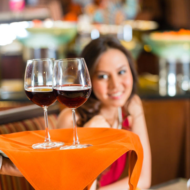 """Waiter serving Chinese woman red wine in fancy restaurant"" stock image"