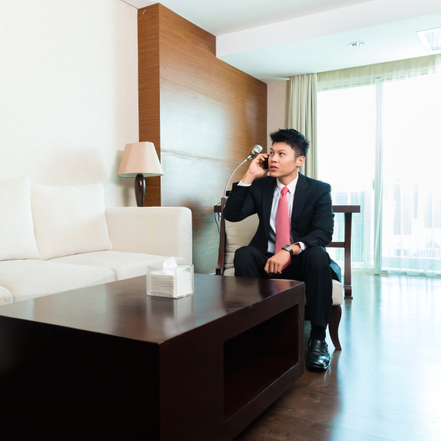 """Chinese Businessman on business trip in hotel suite"" stock image"