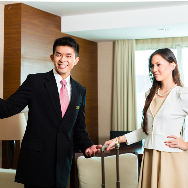 """Asian Chinese hotel manager presenting suite"" stock image"