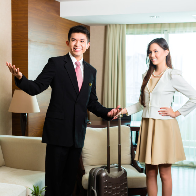 """""""Asian Chinese hotel manager presenting suite"""" stock image"""