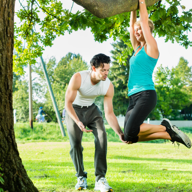 """""""People in city park doing chins or pull ups on tree"""" stock image"""