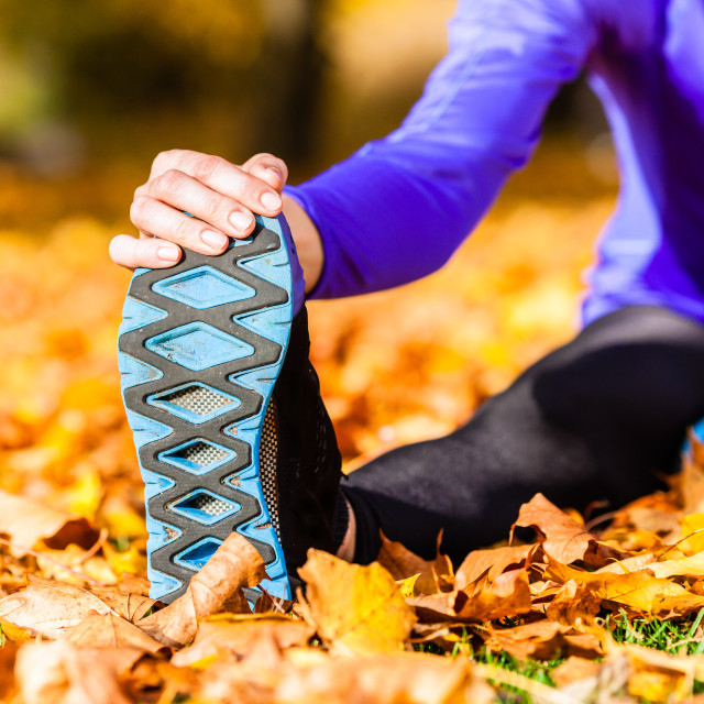 """Sportswoman sport stretching in autumn leaves"" stock image"