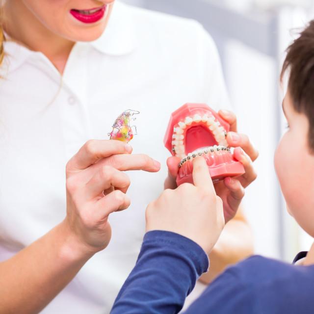 """""""Female Orthodontist explaining boy braces"""" stock image"""