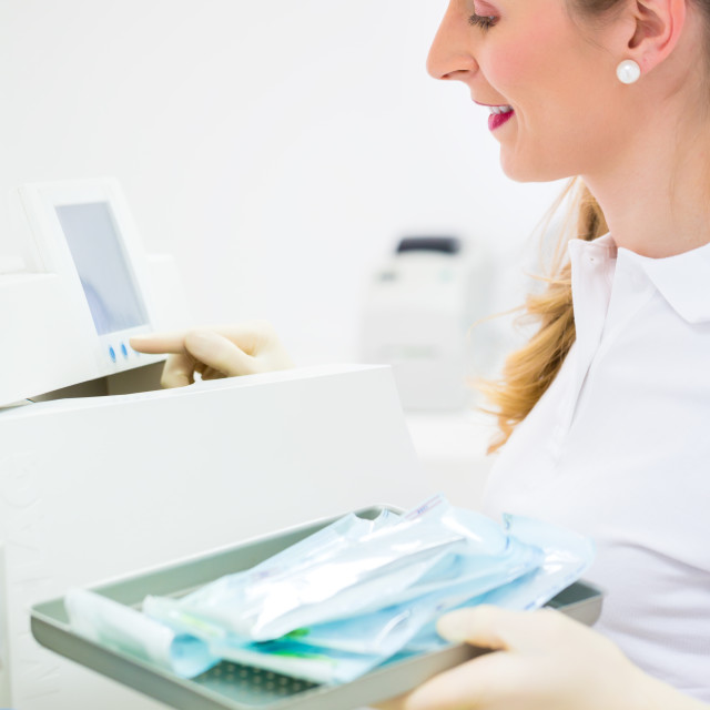 """Assistant with sterile dentist tools"" stock image"