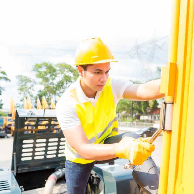 """Asian mechanic repairing construction vehicle"" stock image"