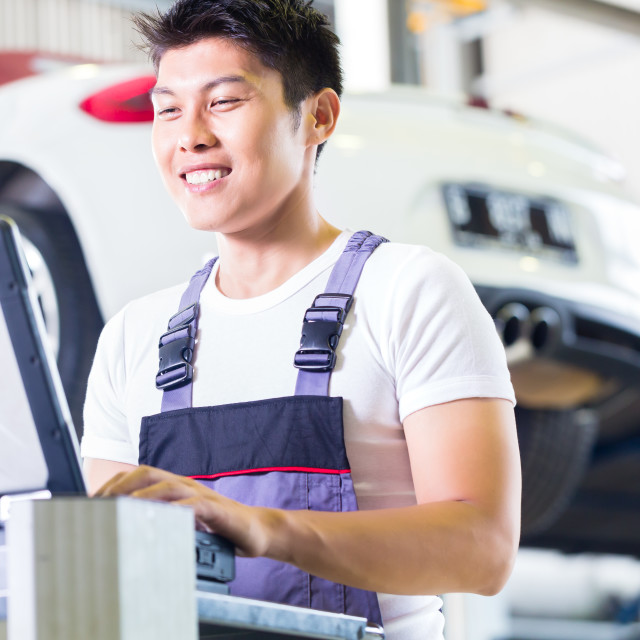 """Car mechanic with diagnosis tool in Asian auto workshop"" stock image"