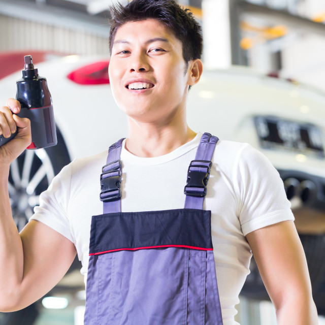 """Car mechanic with tool in Asian Chinese auto workshop"" stock image"