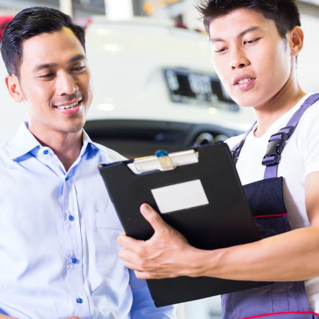 """Car mechanic and customer in Asian auto workshop"" stock image"