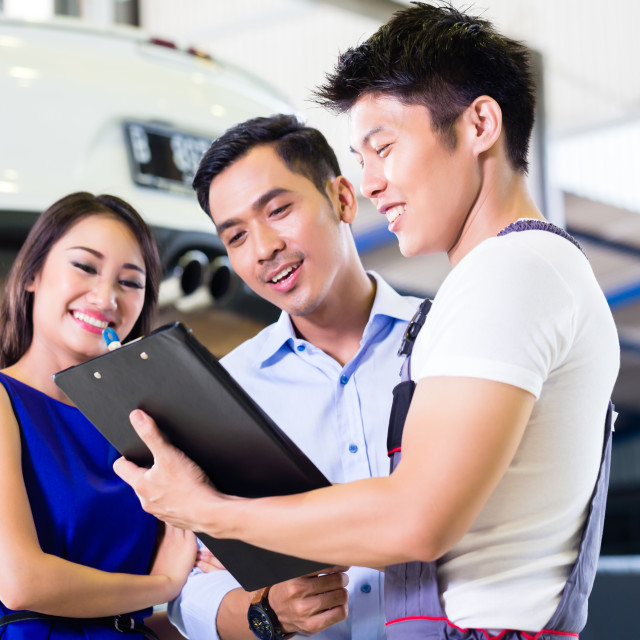 """Car mechanic and Asian customer couple"" stock image"