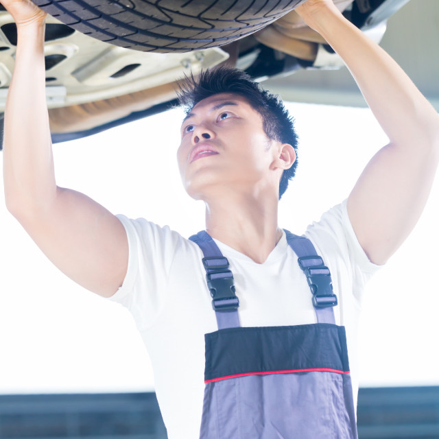 """Asian Chinese car mechanic changing auto tire"" stock image"