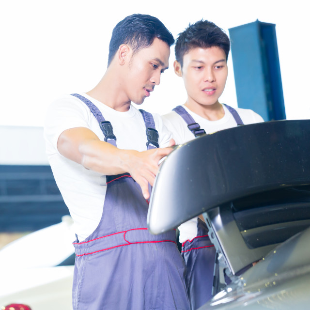 """Car mechanics looking under hood of sports car"" stock image"