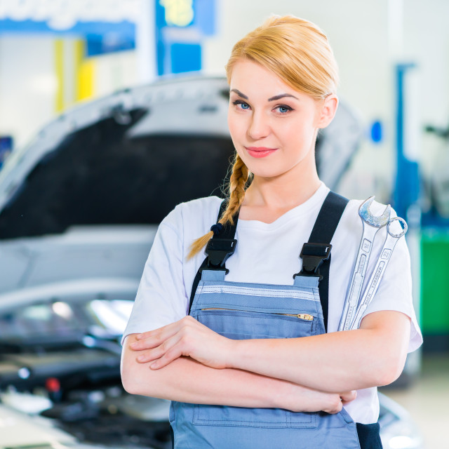 """Female auto mechanic working in car workshop"" stock image"