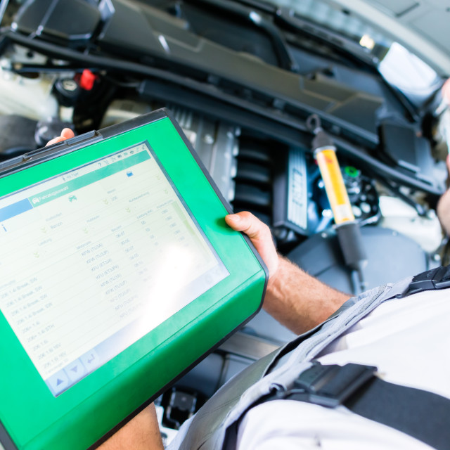 """Mechanic with diagnostic tool in car workshop"" stock image"
