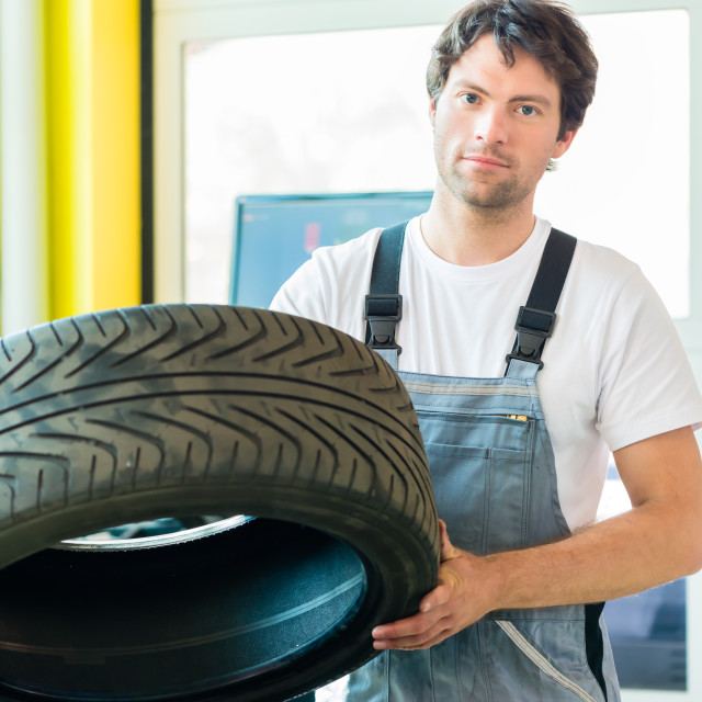 """Auto mechanic changing tire in car workshop"" stock image"