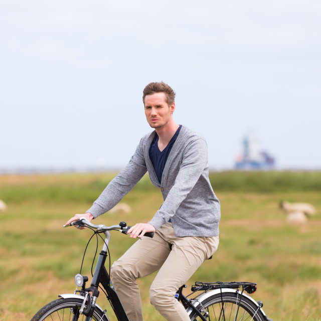 """Man having sea coast bicycle tour at levee"" stock image"