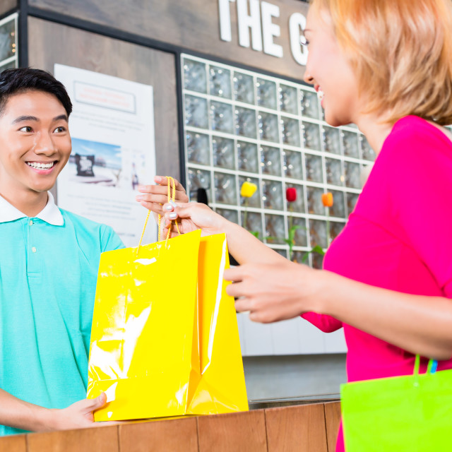 """Shop assistant handing purchase to woman"" stock image"