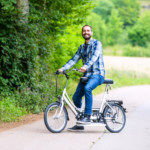 """Man riding tandem bike on country lane"" stock image"
